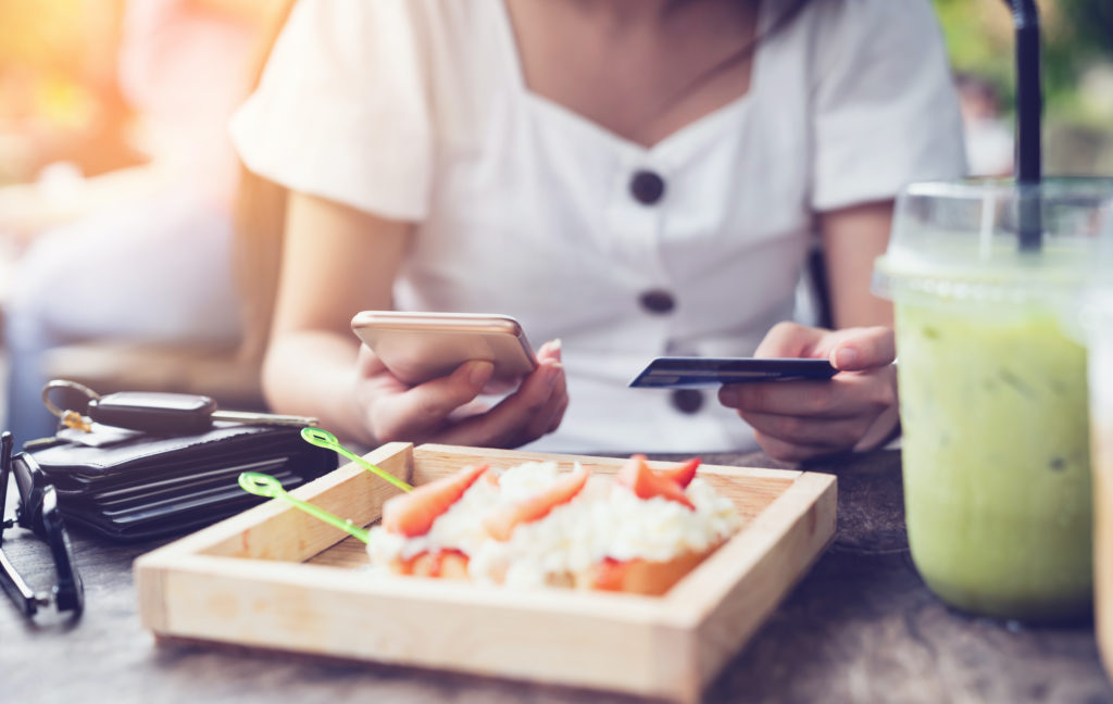Young woman making payment through mobile smart phone with credit card while shopping online in restaurant